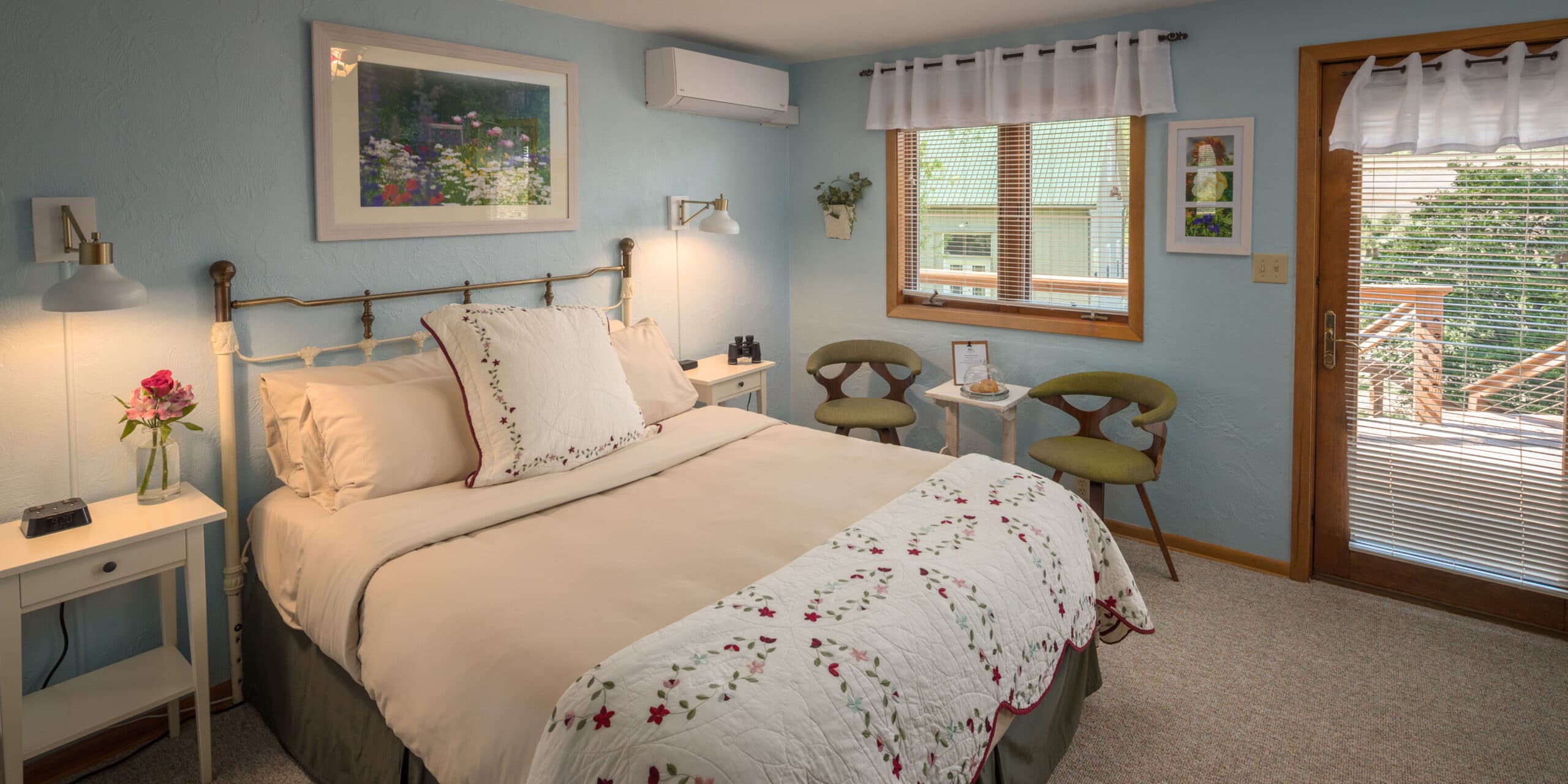 queen sized bed with 2 chairs in light blue room