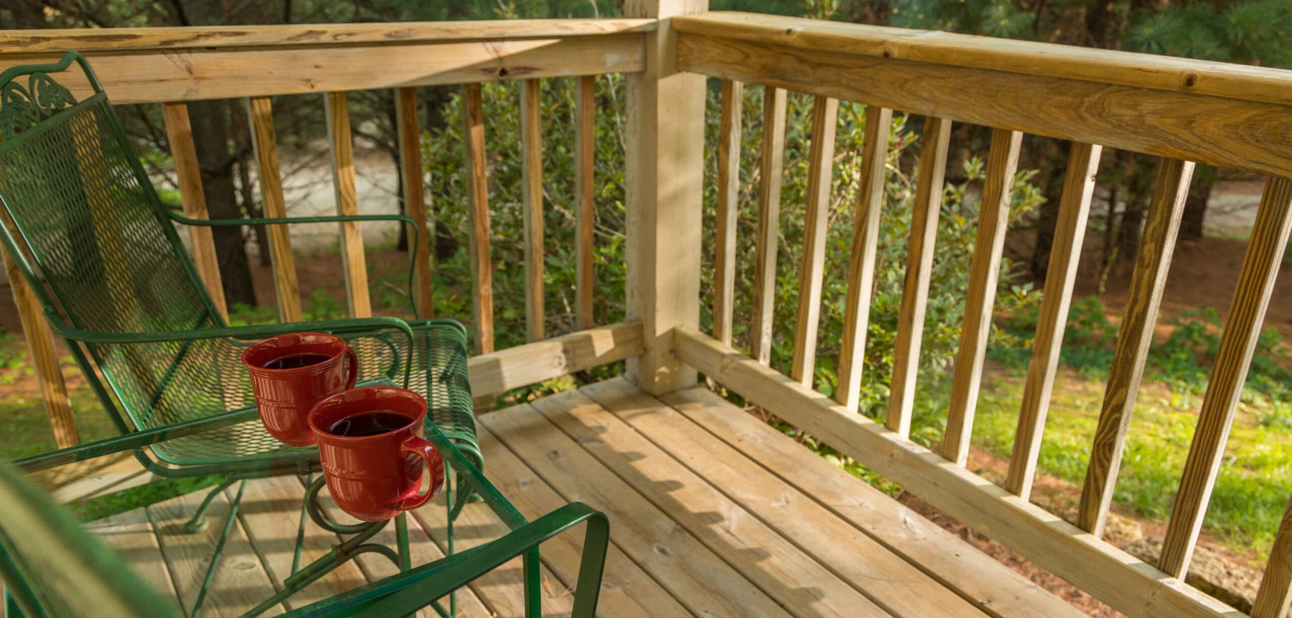 back deck with 2 green chairs and table with coffee cups