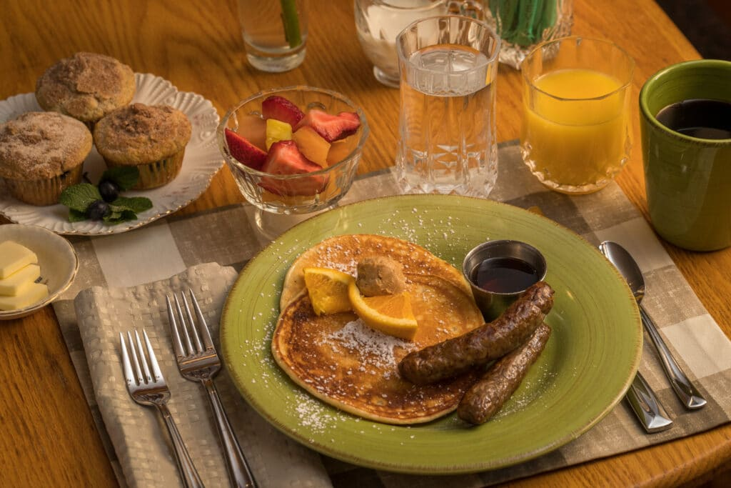pancakes, sausage, fruit, muffins, juice and coffee