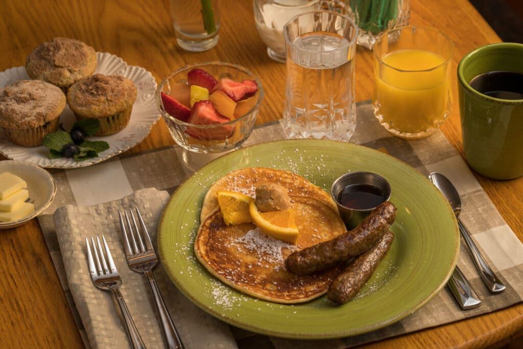 pancakes, sausage, fruit, muffins, juice and coffee