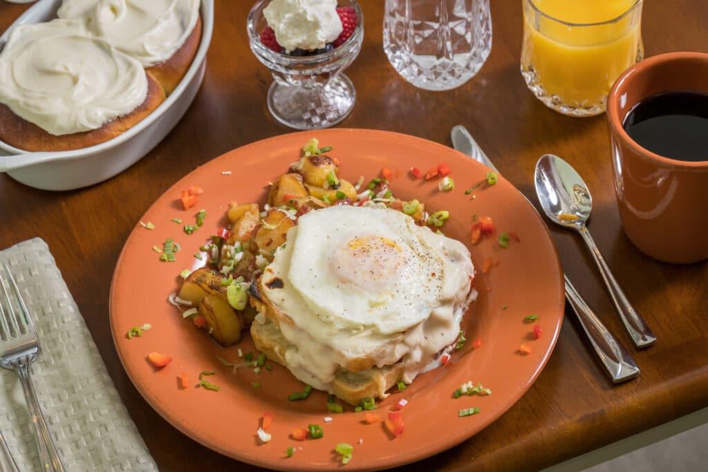 Croque Madame, potatoes, cinamon rolls, fruite, juice and coffee