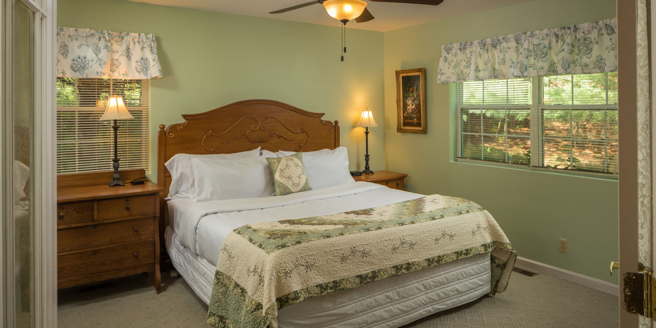 light green room with large white bed with dresser and nightstand