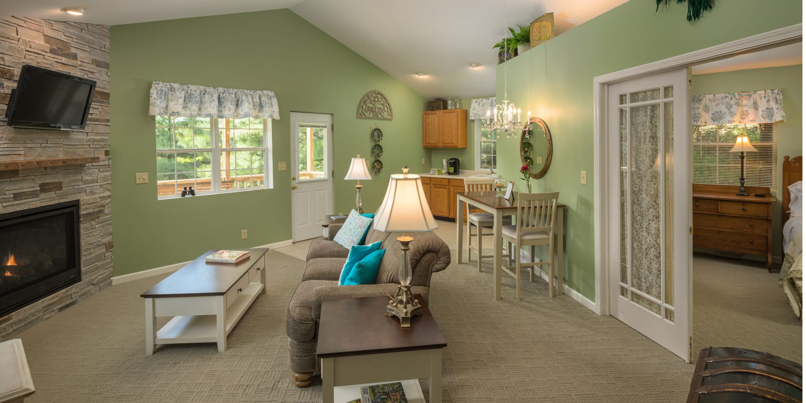 light green walled room with stone fireplace, couch, coffee tables, dining table and kitchenette