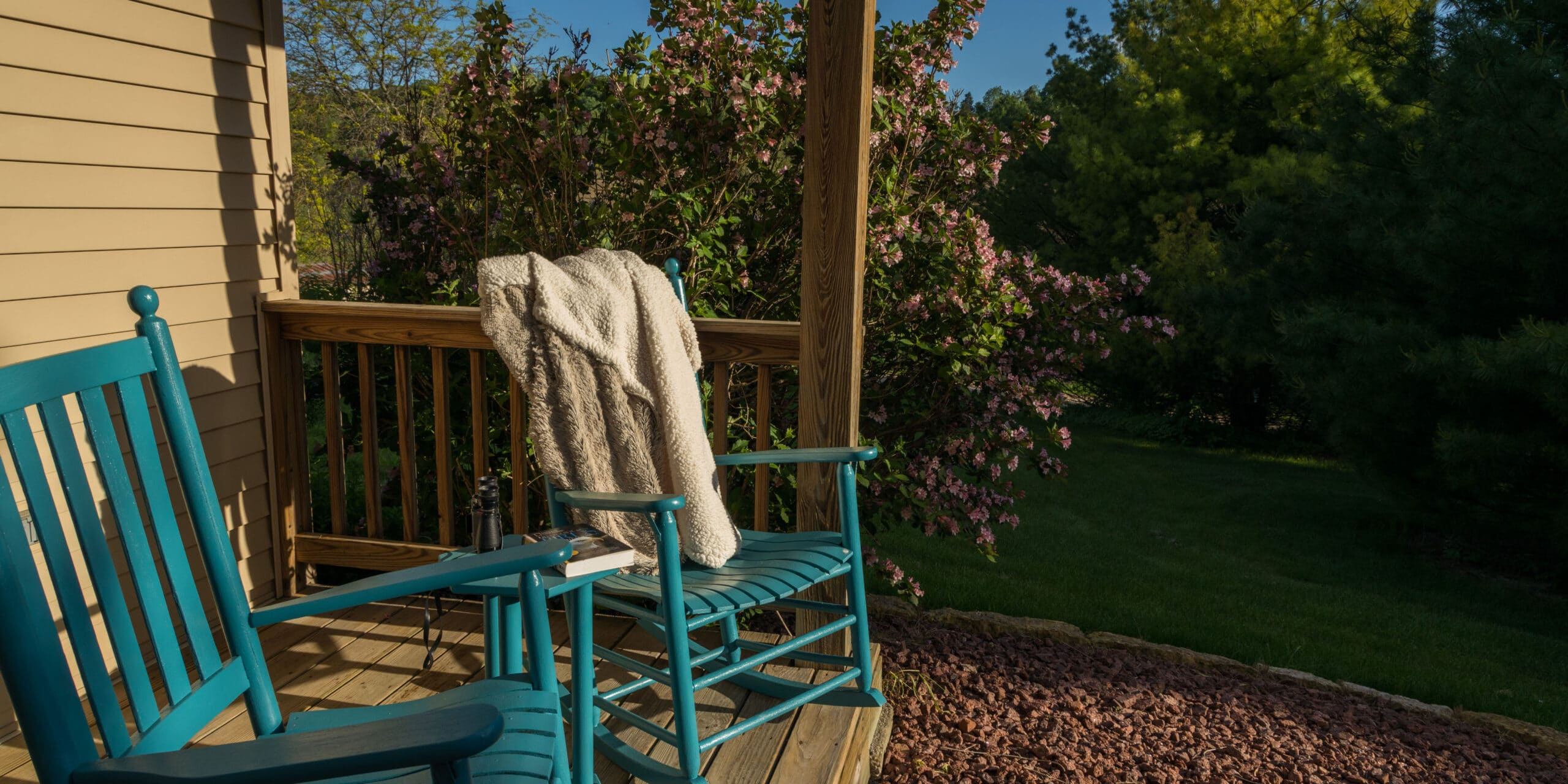 Fox Glen pack porch with blue rocking chairs, a fuzzy throw and pink bush behind