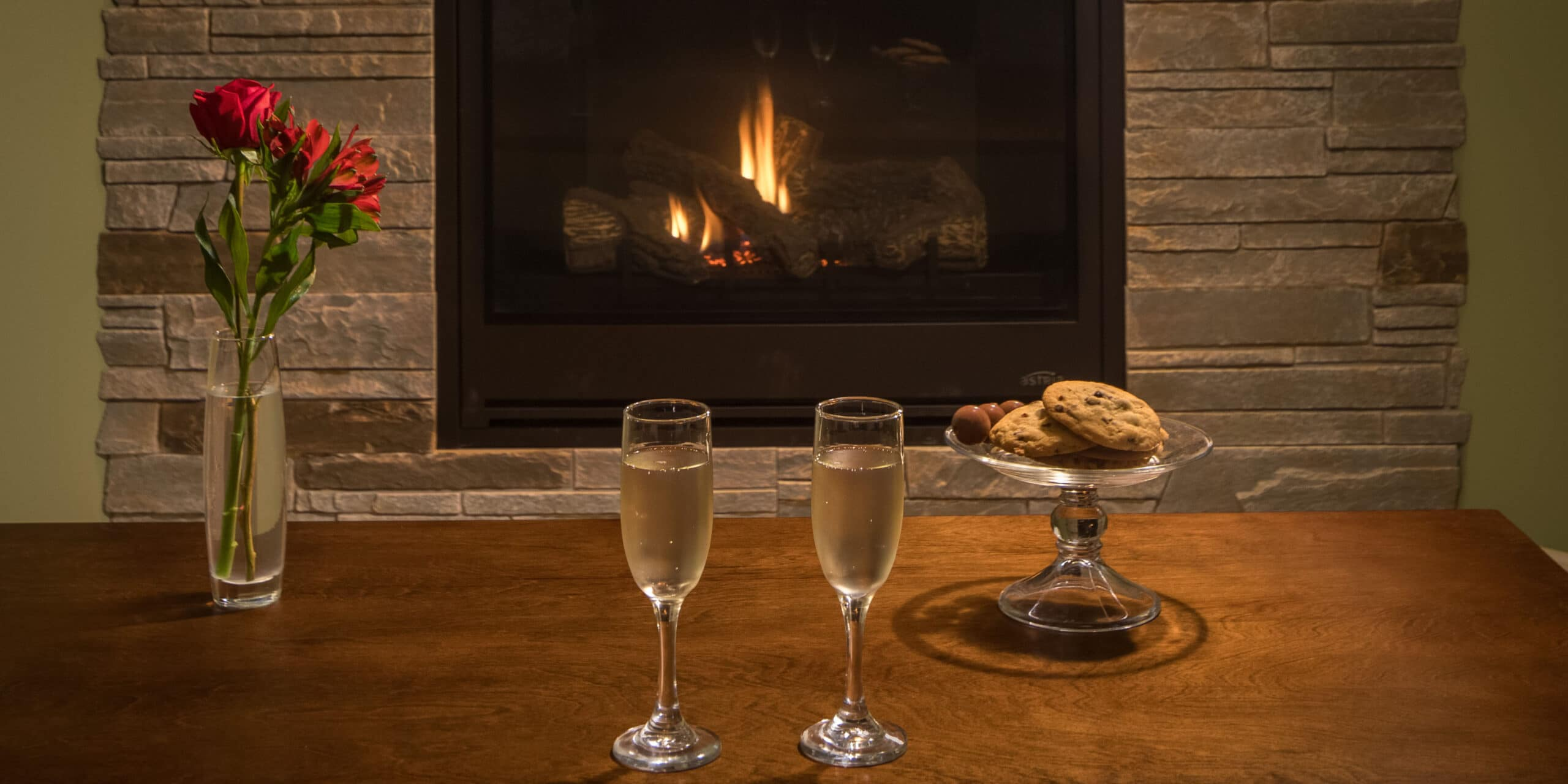 two glasses of champagne, cookies and flowers in front of stone fireplace