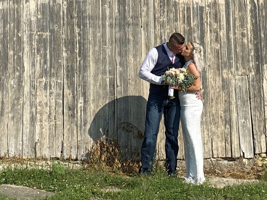 Bride and Groom kissing by barn