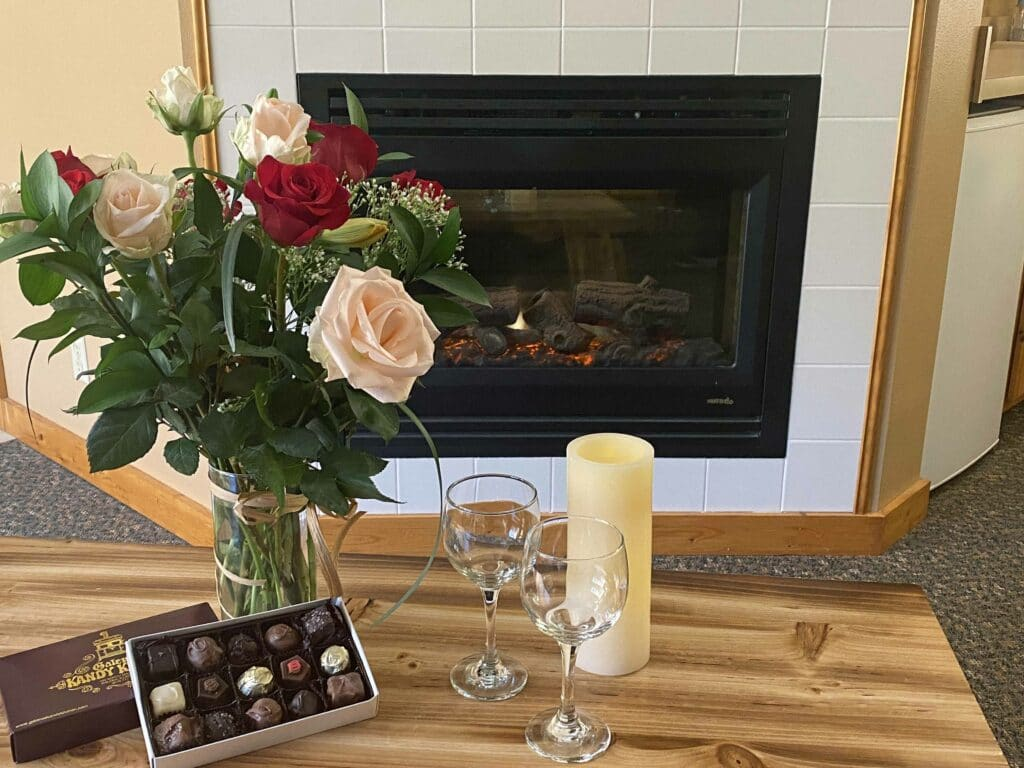 flowers and chocolate in front of a fireplace