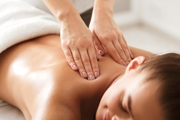 Young woman enjoying therapeutic neck massage in spa center, closeup