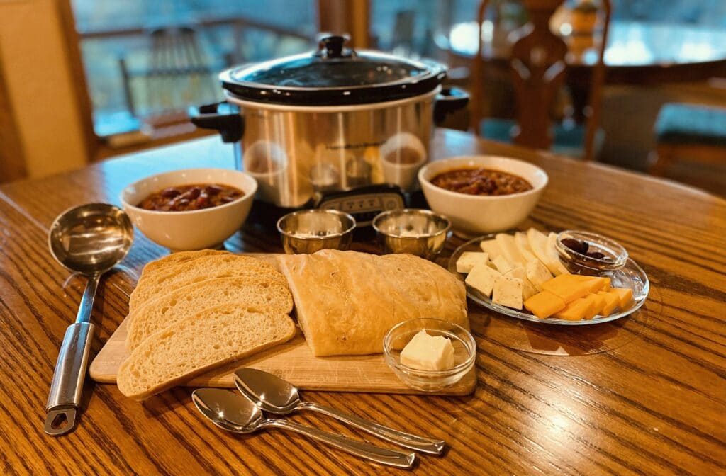 pot of chili , loaf of bread and cheese plate