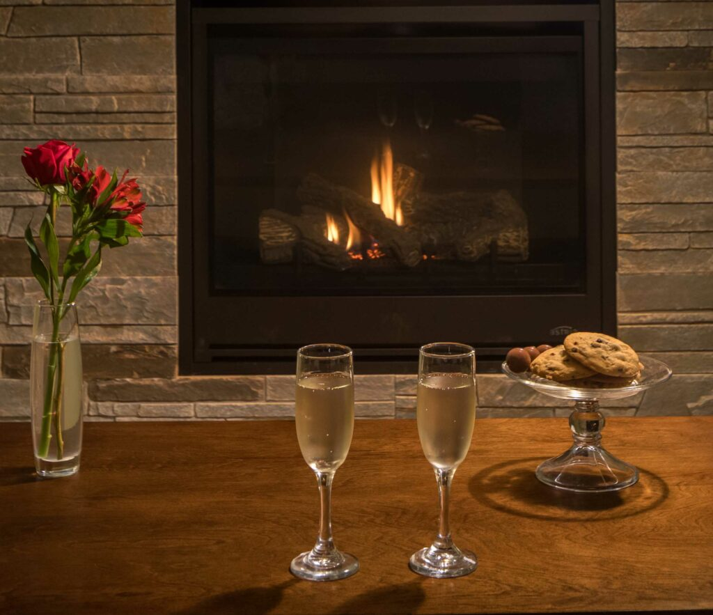 flowers, champagne, and cookies in front of fire