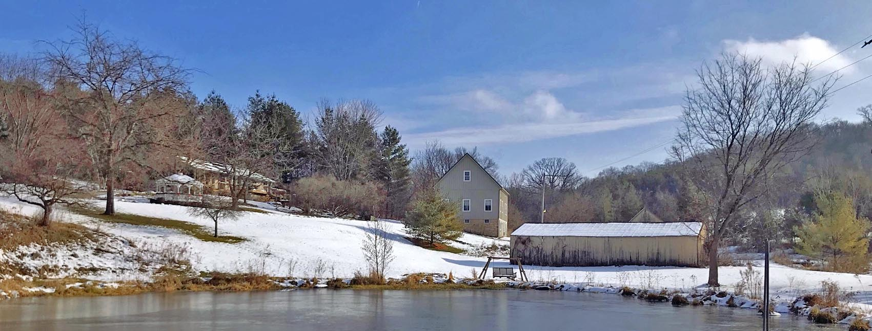 looking at barn and house from pond in winter